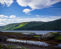 Woman sitting on a rock looking off into the distance in Scotland Stock Images
