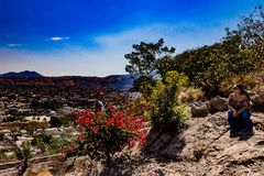 Woman sitting on a rock looking towards the village. Wonderful and sunny day in Tequila Mexico stock image