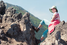 Woman sitting on rock in mountains Stock Photos