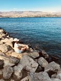 Woman Sitting on Rock Near Body of Water stock images