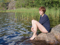 Woman sitting on a rock Stock Images