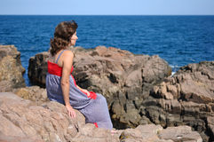 Woman sitting on rock near sea Royalty Free Stock Photography