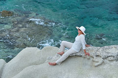 Woman sitting on the rock near the sea Royalty Free Stock Photo