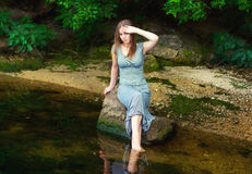 Woman sitting on the rock in a pond Royalty Free Stock Photos