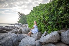 Woman sitting on the rock at the sea shore. Pensive young woman with long hair sitting on the rock at the tropical sea shore near the green trees on Phuket royalty free stock photo