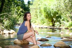Woman sitting on rock by a stream with bare feet in water Stock Photos