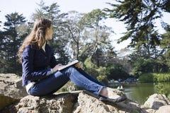 Woman Sitting on Rocks Stock Image