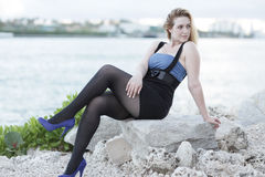 Woman sitting on the rocks Stock Photo