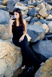 Woman sitting on rocks enjoying italian red wine before party on rocks Royalty Free Stock Photo
