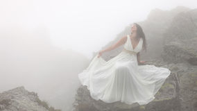Woman sitting on rocks in fog. Beautiful bride in white dress sitting on stones on mountain top surrounded by fog Stock Image