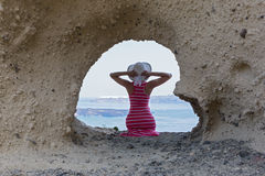 Woman sitting on  rocks , near  cave in the shape of a heart Royalty Free Stock Photo