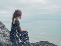 Woman sitting on rocks by the sea Stock Photography