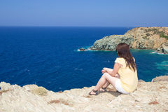 Woman sitting on rocky cliff on sea coast Stock Photo