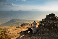 A woman sitting on rocky mountain drinking water and looking out at scenic natural view and beautiful blue sky stock photography