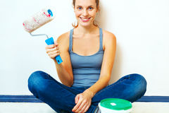 Woman sitting with roller brush Royalty Free Stock Photography