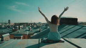 Woman sitting on the roof. City view. Woman sitting on the roof stock footage