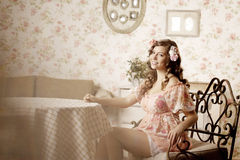 Woman sitting in a room with a vintage interior Stock Image