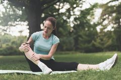 A woman is sitting on a rug for yoga in the park. She was engaged and traumatized her leg. Stock Photos