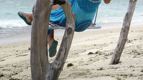 Woman sitting on a rustic, driftwood swing near sea. Close up view of a woman's legs swinging on a rustic, driftwood swing near sea. Gili Air, Indonesia stock video footage