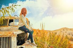 Woman sitting on rusty old classic truck. royalty free stock image