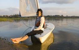 Woman Sitting on Sailboat in Water - Horizontal Royalty Free Stock Image