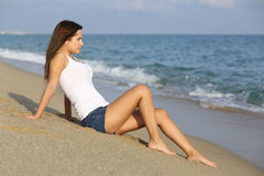 Woman sitting on the sand of the beach Stock Photos
