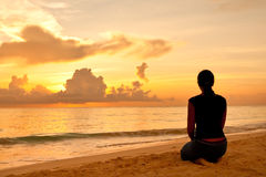 Woman sitting on a sand beach in front of sunset Royalty Free Stock Images