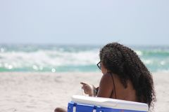 Woman Sitting on Sand Beside Blue and White Cooler Box Near Shore Stock Images