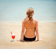 Woman sitting on sand with cocktail Stock Image