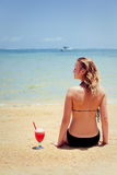 Woman sitting on sand with cocktail Royalty Free Stock Photo