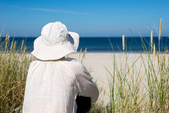 Woman sitting on sand dune and looking at sea Stock Photos