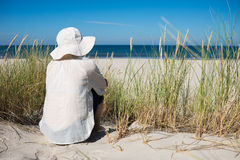 Woman sitting on sand dune and looking at sea Royalty Free Stock Photo