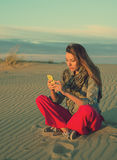 Woman sitting on a sand dune with a smartphone Stock Photography