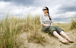 Woman sitting in sand dunes Stock Images