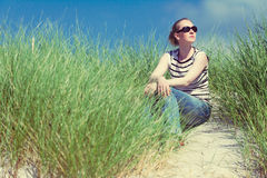 Woman sitting in sand dunes amongst tall grass relaxing, enjoying the view on sunny day Royalty Free Stock Images