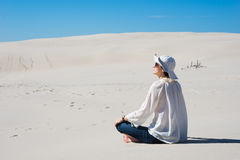 Woman sitting on sand and looking at sky Royalty Free Stock Photo