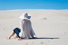 Woman sitting on sand and looking at sky Stock Photography