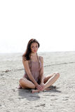 Woman sitting on the sand Stock Photography