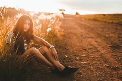 Woman Sitting on Sand Surrouded by Kans Grass during Sunset stock photo