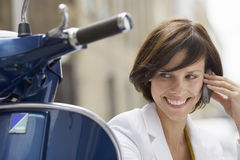 Woman sitting beside scooter, using mobile phone, smiling, close-up Stock Photos