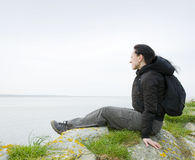 Woman sitting on sea cliff Stock Photos