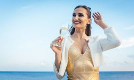 Woman sitting by the sea at a party on beach Royalty Free Stock Image