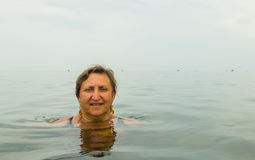 Woman sitting in a sea in the rain Royalty Free Stock Image
