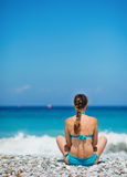 Woman sitting on sea shore Stock Images