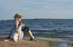 Woman sitting on sea shore with dog Stock Photo