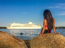 Woman Sitting By The Sea Watching A Cruise Ship. A woman sitting by the sea watching a cruise ship royalty free stock images