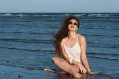 Woman sitting in sea water wear bikini, sunglasses and white shirt Royalty Free Stock Photography