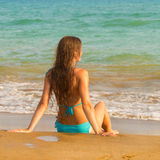 Woman sitting on seacoast in the surf line. Stock Image