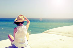 Woman sitting on the seaside. Holding his hat Stock Photos