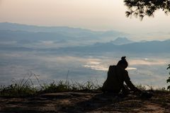 Woman sitting serenely of the cliff and looking at the valley and mountains. In the morning Royalty Free Stock Images